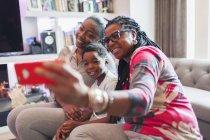 Família de várias gerações tirando selfie com telefone de câmera na sala de estar — Fotografia de Stock