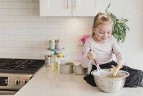 Souriant fille cuisson sur comptoir de cuisine — Photo de stock