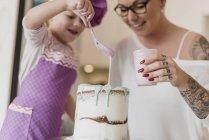 Мать и дочь украшают торт — стоковое фото