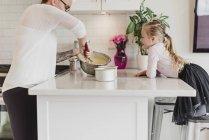 Допитлива дівчина спостерігає за матір'ю випічки в кухні — стокове фото