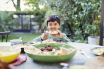 Portrait happy boy eating naan bread at patio table — Stock Photo