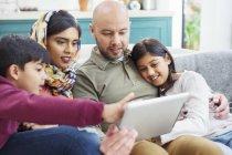 Famiglia con tablet digitale sul divano — Foto stock