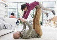 Отец поднимает сына с ногами на полу в гостиной — стоковое фото