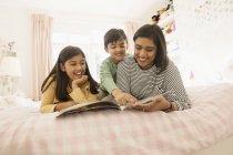 Libro di lettura della madre ai bambini sul letto — Foto stock