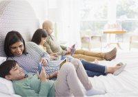 Семья с использованием технологии на кровати — стоковое фото