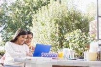 Sorrindo mãe e filha usando laptop na mesa — Fotografia de Stock