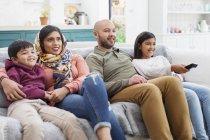 Famiglia guardando la TV sul divano del soggiorno — Foto stock