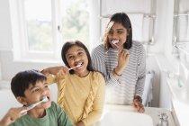 Ritratto famiglia felice spazzolatura denti in bagno — Foto stock