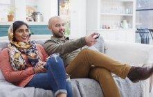 Coppia guardare la TV sul divano soggiorno — Foto stock