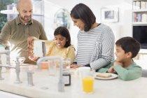 Family enjoying breakfast in kitchen — Stock Photo