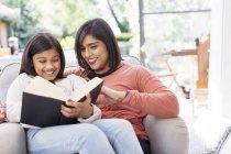 Madre e figlia lettura libro in poltrona — Foto stock