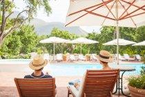 Couples détendant sur des chaises de salon au Sunny Resort Poolside — Photo de stock