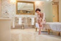 Жінка надягаючи високий каблук сандалі в розкішному готельному ванній кімнаті — стокове фото