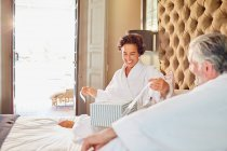 Husband watching happy wife opening gift on hotel bed — Stock Photo