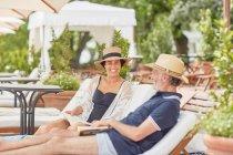 Coppia matura che legge libri, relax sulle sedie a sdraio del resort a bordo piscina — Foto stock