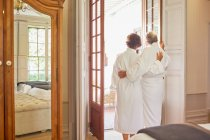 Mature couple in spa bathrobes standing at hotel balcony doorway — Stock Photo