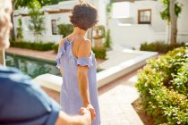 Couple holding hands, walking at sunny poolside — Stock Photo