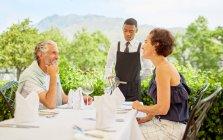 Vinho mordomo derramando vinho para casal maduro jantando na mesa do pátio — Fotografia de Stock