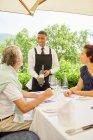 Wein-Steward zeigt Weinflasche an Patio-Tisch — Stockfoto