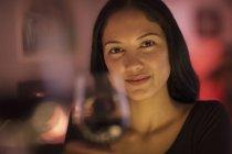 Портрет впевненою молодою жінкою, яка тримає келих вина — стокове фото
