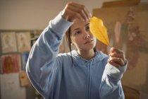 Curious female artist examining autumn leaf — Stock Photo