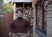 Портретна людина перевозять дрова на осінній дворик — стокове фото