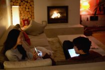 Couple using smart phone and digital tablet in dark living room — Stock Photo