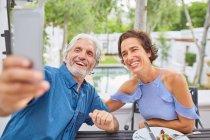 Couple d'âge mûr prenant selfie avec téléphone caméra sur le patio de l'hôtel — Photo de stock