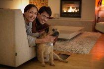 Портрет счастливая пара с собакой в гостиной — стоковое фото