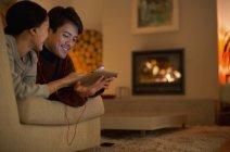 Щаслива пара з навушниками обмін цифровий планшет на вітальні диван — стокове фото