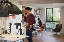 Мужчина-фотограф работает в студии, берет перерыв на кофе — стоковое фото