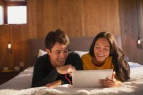 Happy young couple with headphones sharing digital tablet on bed — Stock Photo