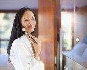 Retrato confiante jovem mulher aplicando maquiagem no espelho do banheiro — Fotografia de Stock