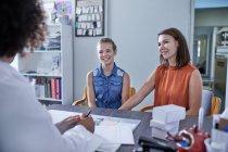Matriz e filha de sorriso que falam com a filha no escritório dos doutores da clínica — Fotografia de Stock