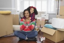 Portrait happy mother and daughter hugging, moving into new house — Stock Photo