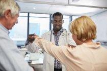 Homme médecin examinant les patients âgés épaule dans la salle d'examen clinique — Photo de stock