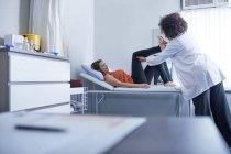 Жіночий лікар вивчення ніг пацієнта в екзаменаційна кімната клініки — стокове фото