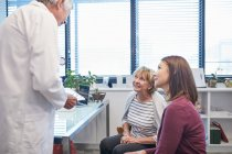 Doctor with digital tablet talking with women in doctors office — Stock Photo