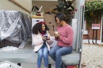 Mère et fille buvant du thé à l'arrière du van en mouvement — Photo de stock