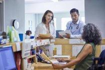 Ärzte und Rezeptionistin im Gespräch in der Klinik — Stockfoto