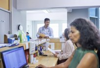 Врач и администратор беседуют на приеме в клинике — стоковое фото