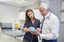 Врач и медсестра с цифровым планшетом разговаривают в кабинете клиники — стоковое фото