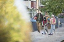 Muslimische Familie läuft und fährt Roller auf Bürgersteig — Stockfoto