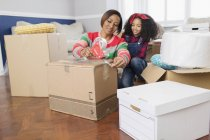 Mother and daughter taping moving boxes, moving house — Stock Photo
