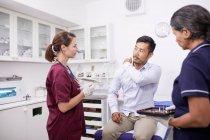 Paciente masculino explicando dolor de hombro a doctora en sala de examen clínico - foto de stock