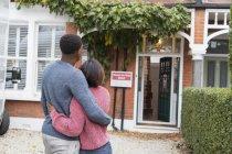 Feliz, cariñosa pareja abrazándose fuera de casa nueva - foto de stock