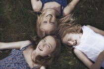 Портрет счастливые сестры лежа в траве — стоковое фото