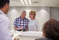 Casal sénior a fazer check-in, a preencher papelada na recepção da clínica — Fotografia de Stock