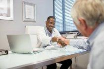 Maschio medico stringendo la mano con il paziente anziano in ufficio medici — Foto stock