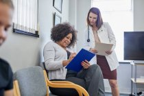 Female doctor and patient discussing paperwork in clinic waiting room — Stock Photo